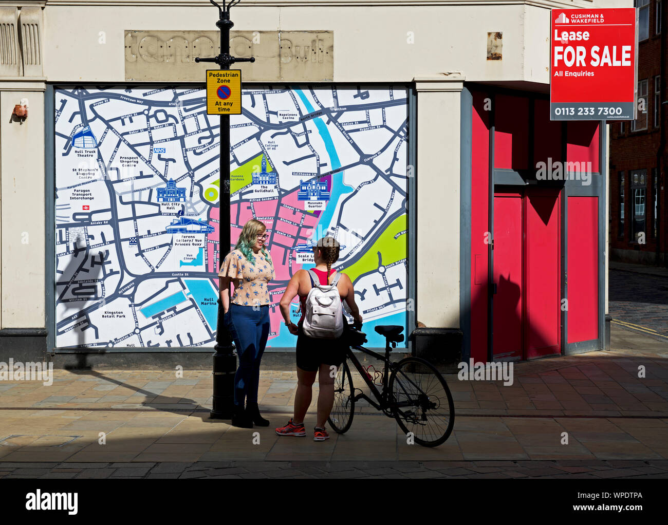 two-young-women-chatting-on-prospect-street-in-front-of-a-map-of-the-city-hull-east-yorkshire-england-uk-WPDTPA.jpg
