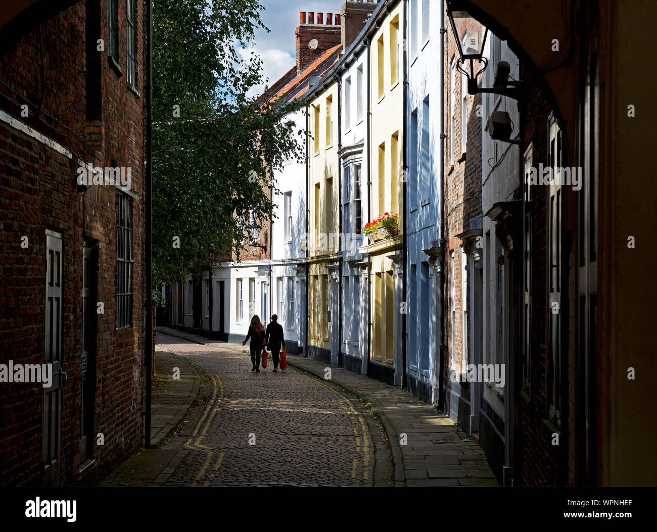 two-young-women-walking-past-the-georgian-houses-on-cobbled-prince-street-hull-east-yorkshire-england-uk-WPNHEF.jpg