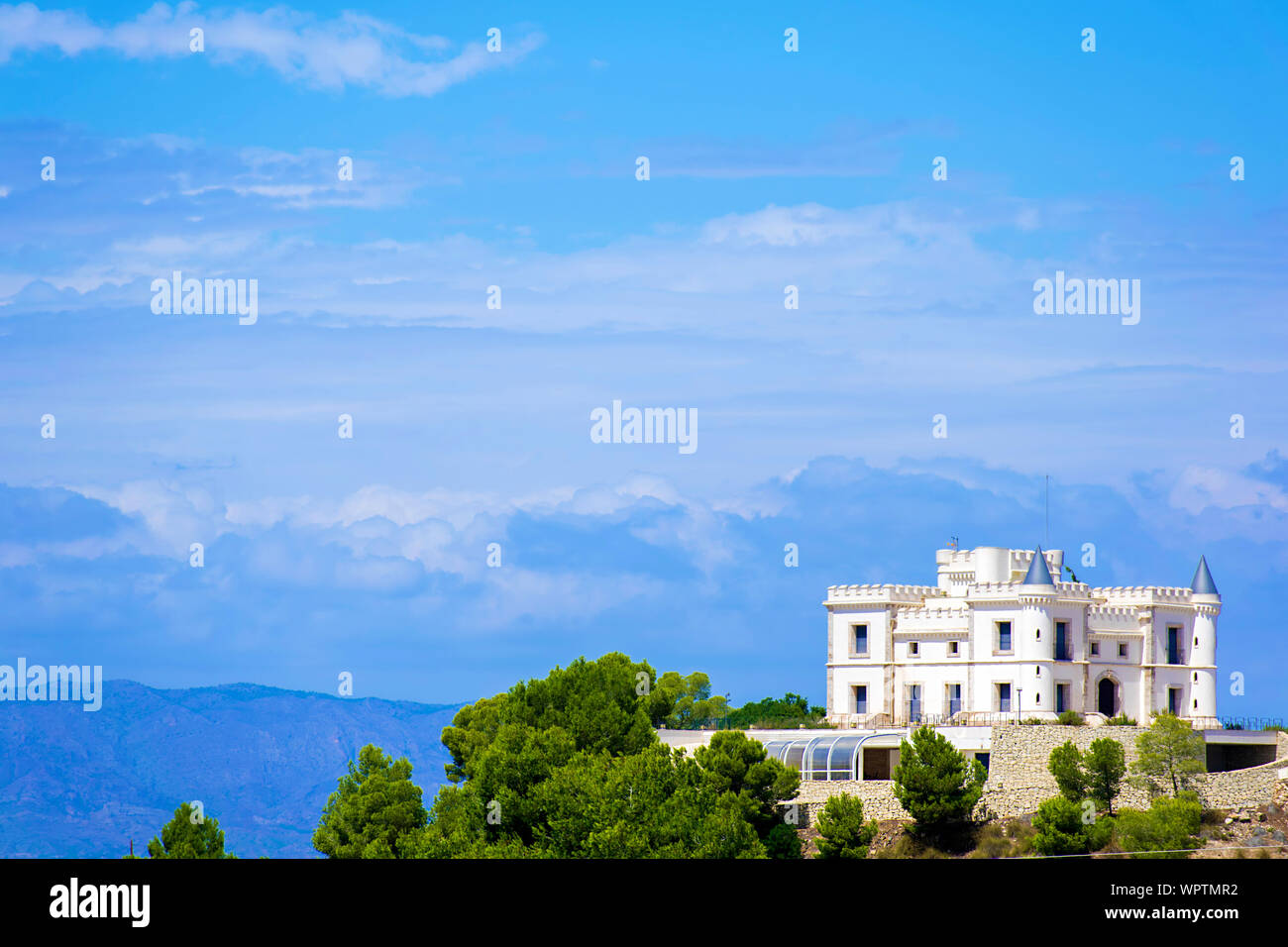 Ancient white castle located at the top of a mountain Stock Photo