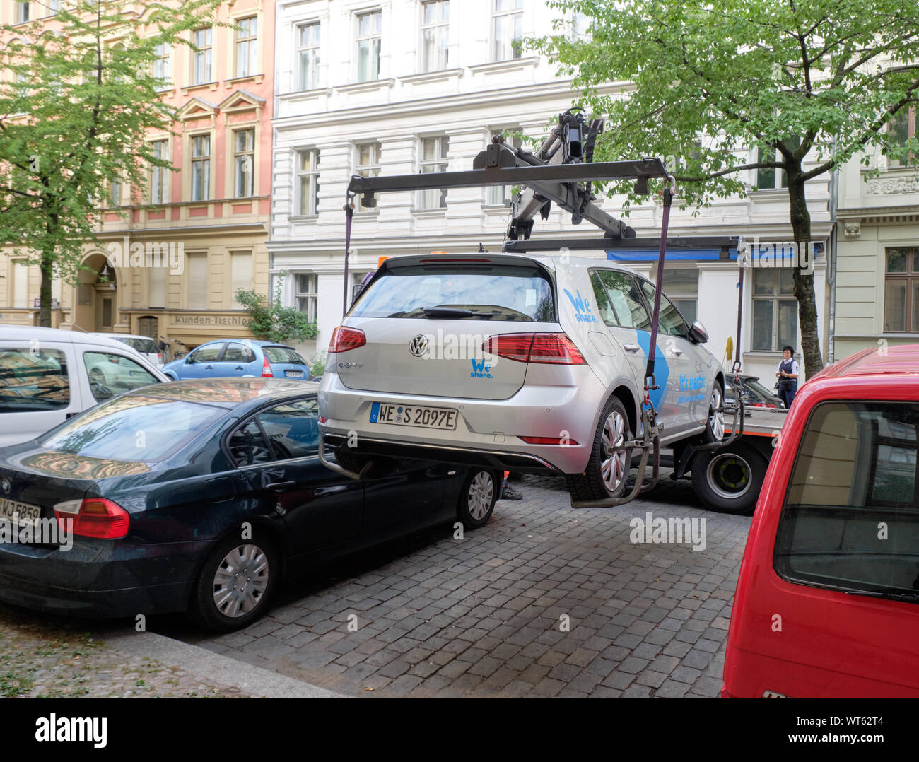 electric-car-sharing-vehicle-being-lowered-in-parking-spot-by-towing-crane-by-employee-berlin-germany-WT62T4.jpg