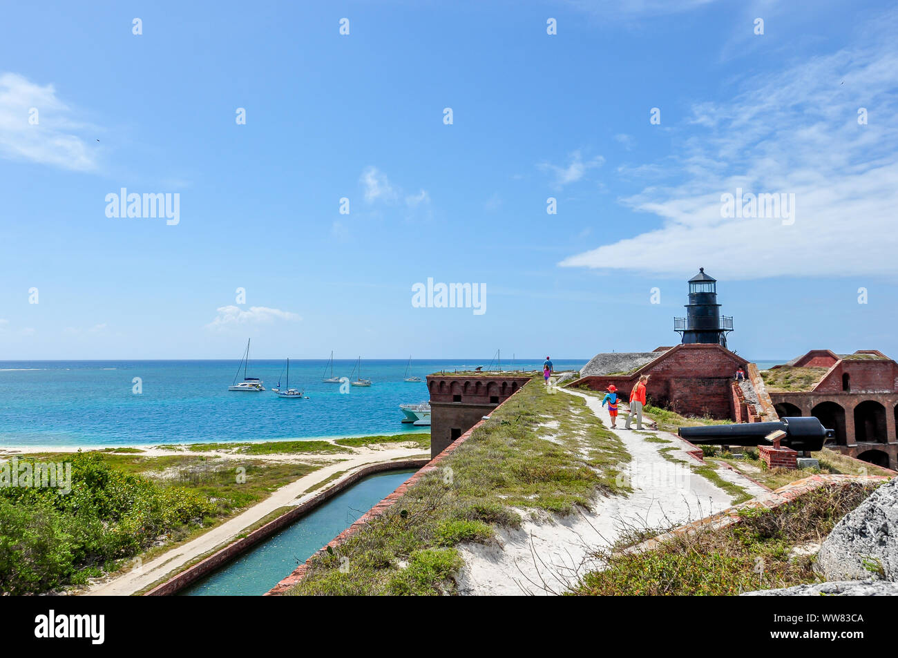 Kids explore Fort Jefferson at Dry Tortugas National Park with their father, walking along the roof with view of lighthouse, water and sailboats. Stock Photo