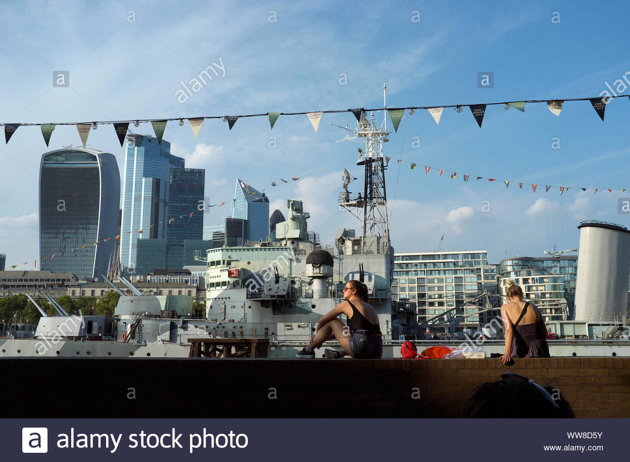 The WWII navy ship HMS Belfast, almost hidden against the backdrop across the River Thames. South Bank, London, UK. Stock Photo