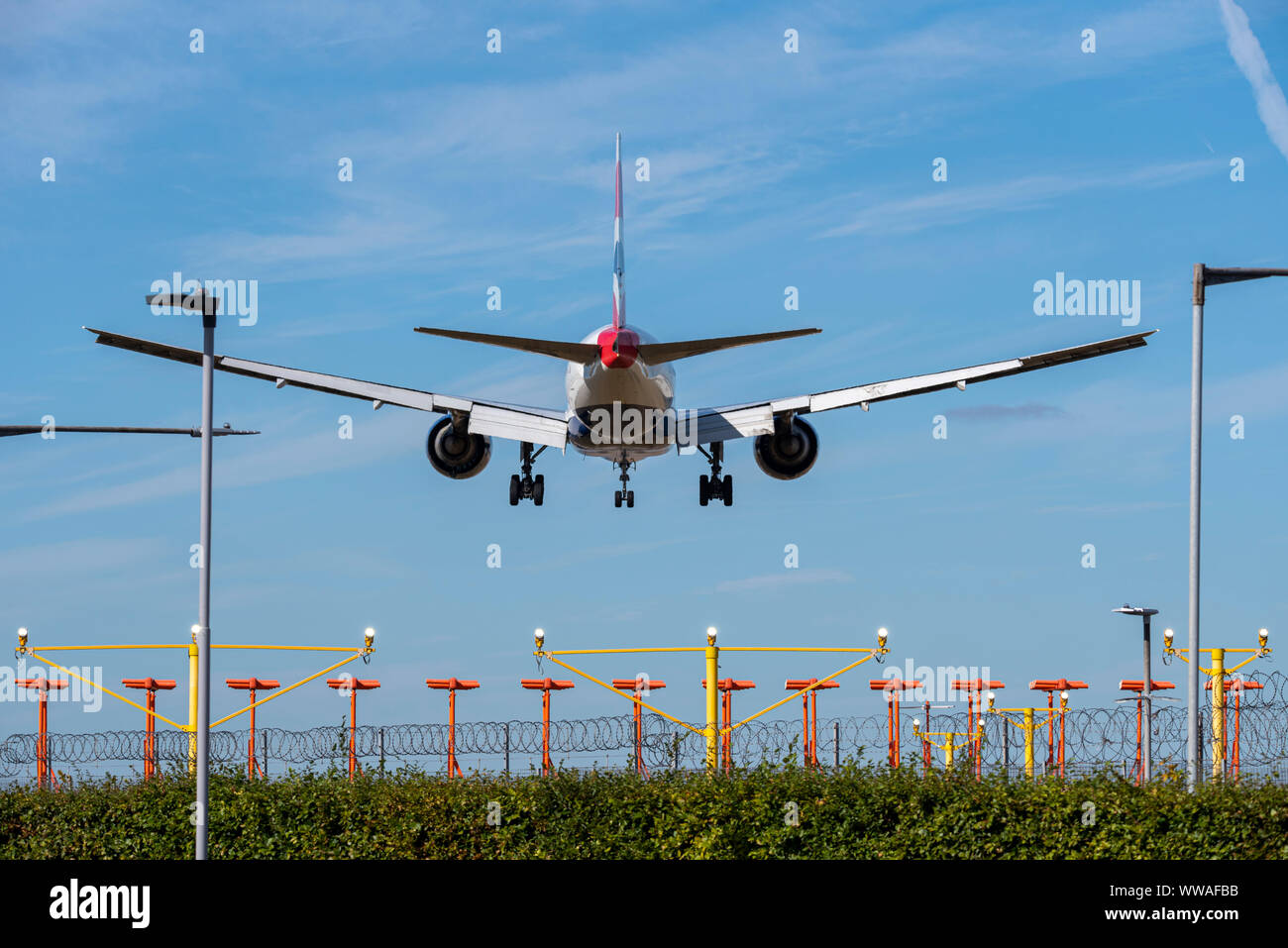 british-airways-jet-airliner-plane-landing-at-london-heathrow-airport-in-hounslow-london-uk-behind-runway-approach-threshold-lights-space-for-copy-WWAFBB.jpg