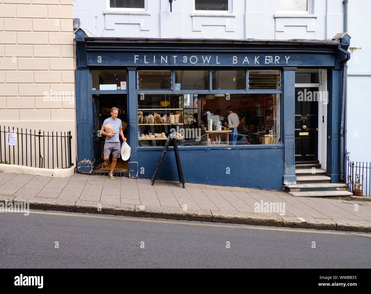 person-coming-out-of-flint-owl-bakery-on-inclined-high-street-lewes-carrying-bread-purchase-from-establishment-lewes-uk-september-2019-WWBB35.jpg