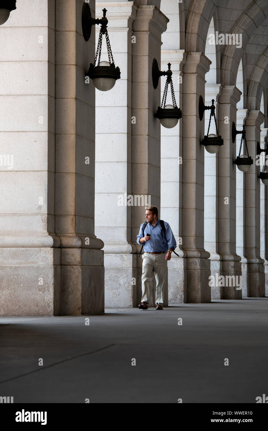 usa-washington-dc-union-station-train-station-a-lone-commuter-walking-with-a-backpack-and-with-headphones-and-phone-in-the-arcade-WWER10.jpg