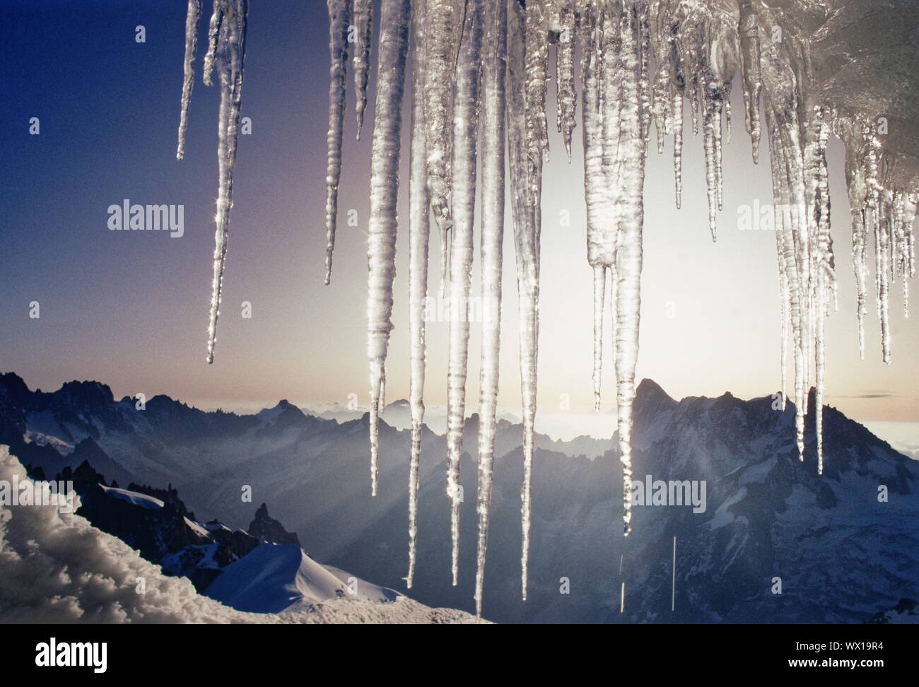 The sun rising behind icicles in the French Alps Stock Photo