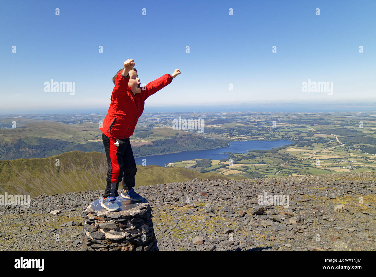 a-young-boy-7-yrs-old-celebrates-on-reaching-the-summit-of-skiddaw-a-mountain-in-the-lake-district-cumbria-uk-WX1NJM.jpg