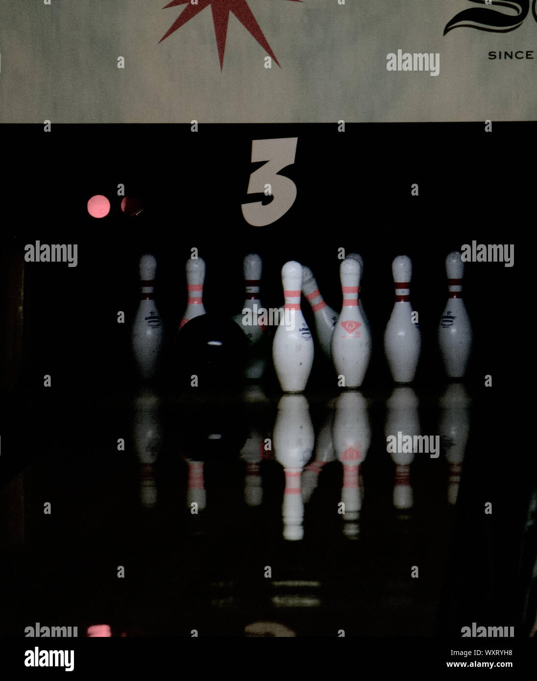 Bowling lane with bowling ball striking bowling pins with red stripes. Park Tavern bowling and entertainment center. St. Louis Park, Minnesota, USA. Stock Photo