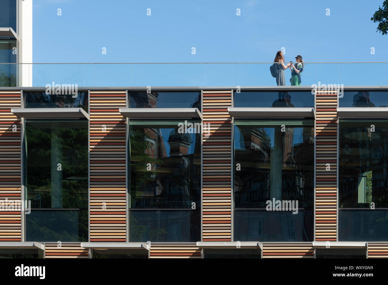 two-female-students-having-a-conversation-on-the-roof-of-the-emily-wilding-davison-building-at-royal-holloway-college-surrey-uk-WXYGN9.jpg