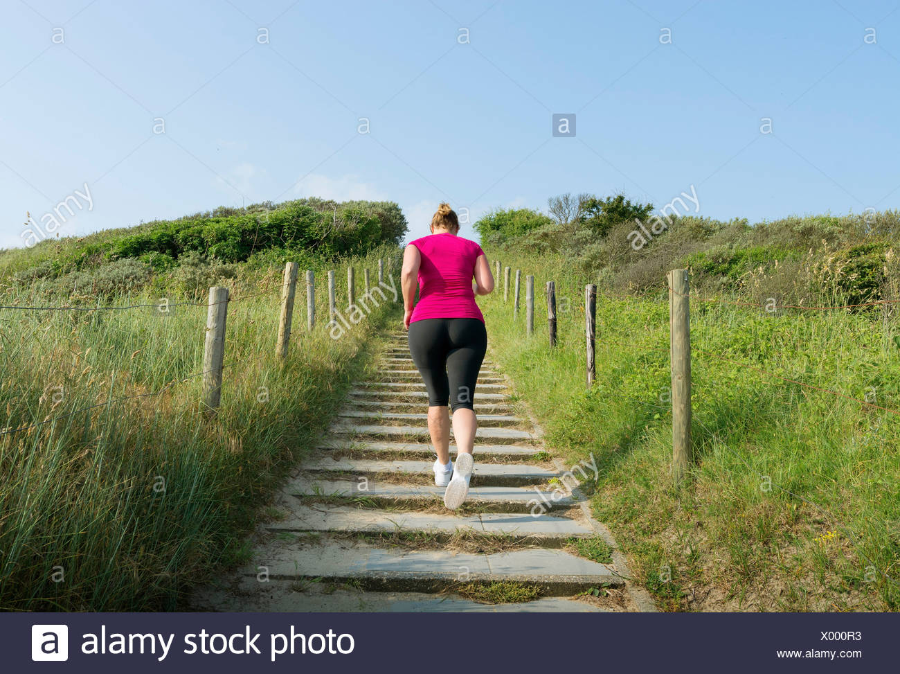 Rear view of woman running up stairs - Stock Image