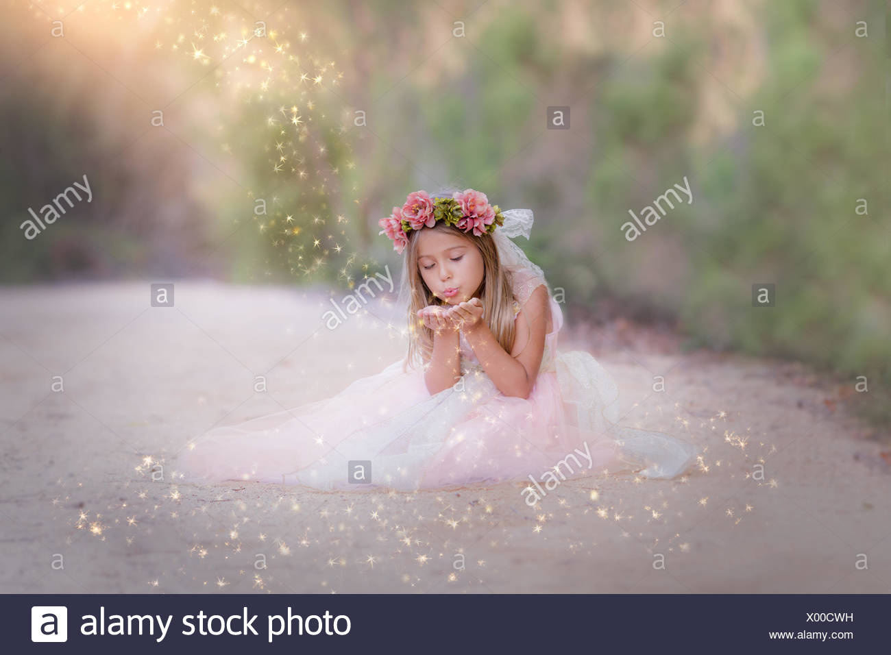 Girl sitting in the road, blowing glitter - Stock Image