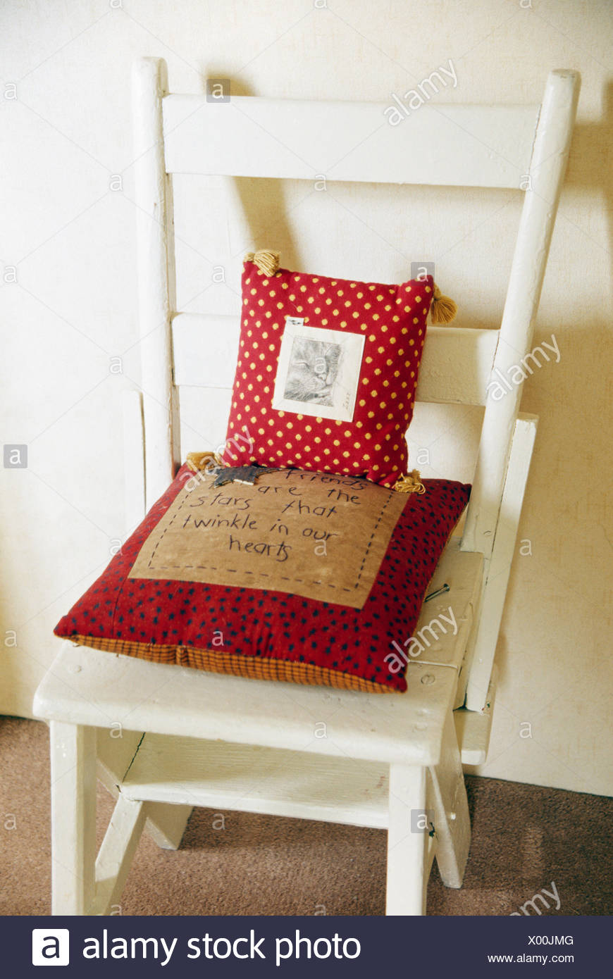 Close Up Of Red Appliqued Cushions On Cream Painted Folding Chair