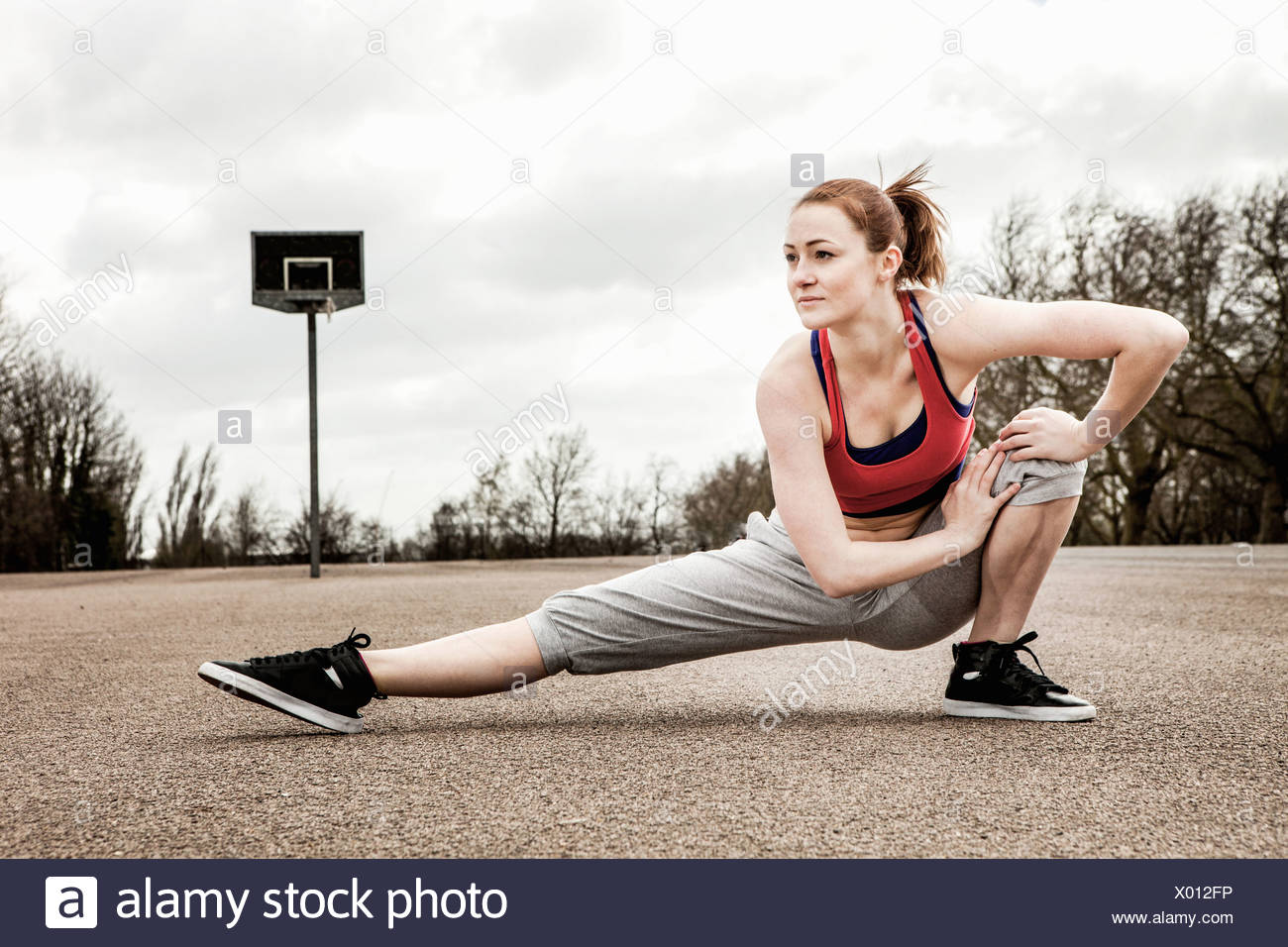 Woman stretching left leg and bending right leg on court - Stock Image