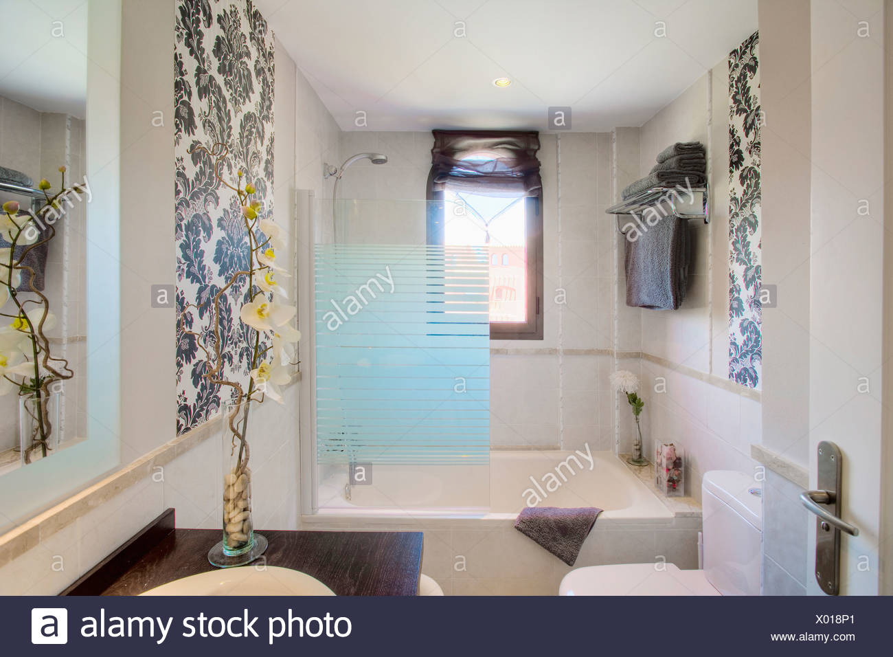 Small Modern Bathroom With Opaque Glass Shower Screen On Bath And Large Leaf Print Wallpaper On Two Walls