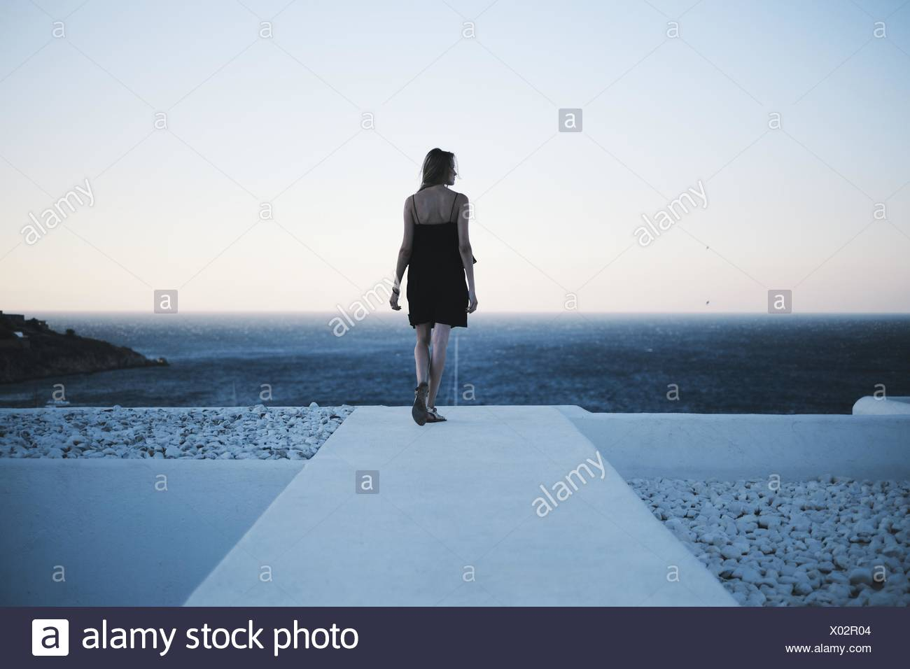 Rear view of woman looking out to sea - Stock Image