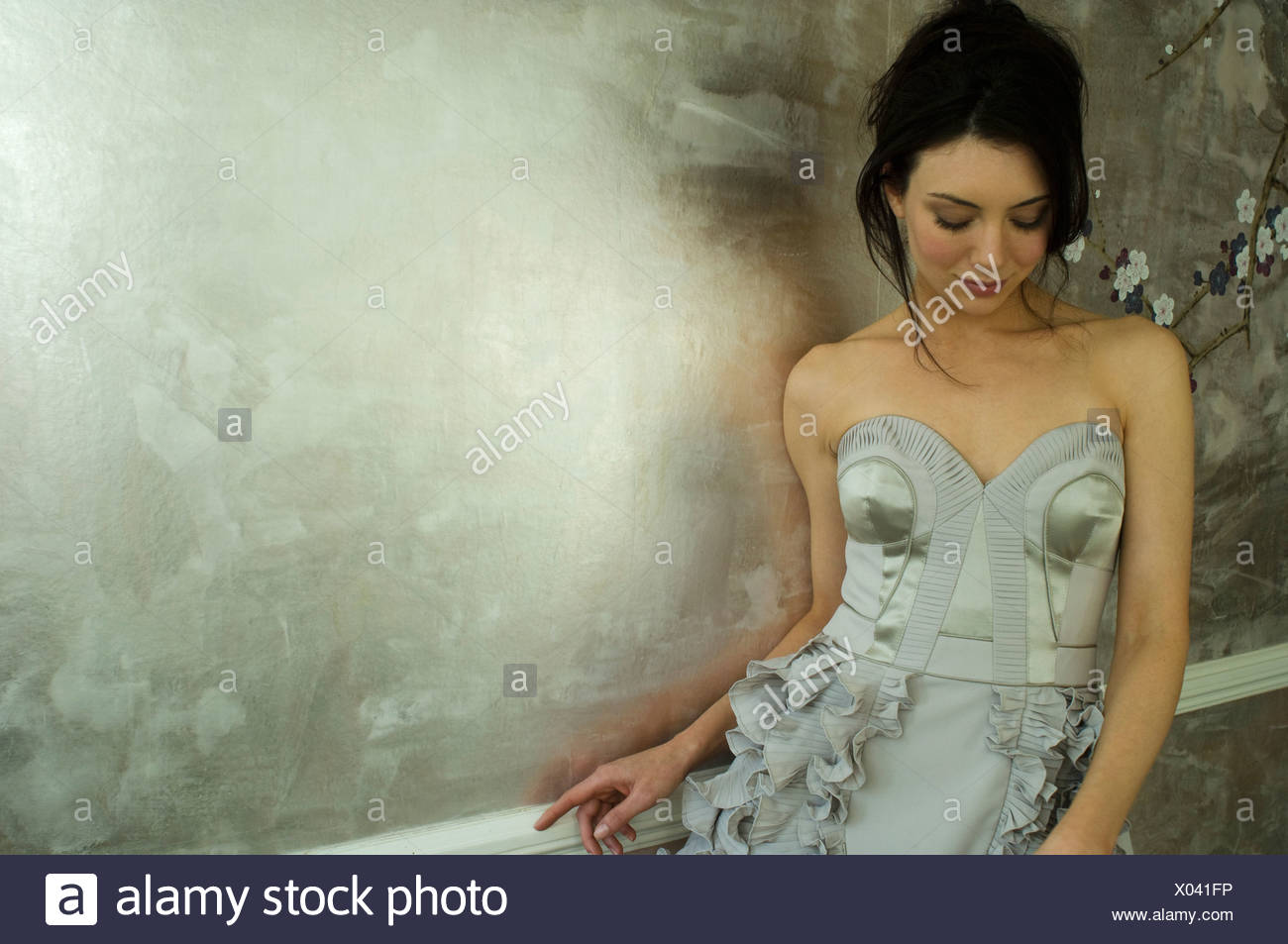 Woman wearing gown by ornate wallpaper - Stock Image