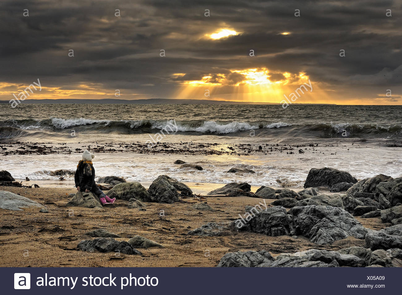 Ireland, Munster, County Waterford, Tramore, Girl (4-5) sitting on rock at beach - Stock Image