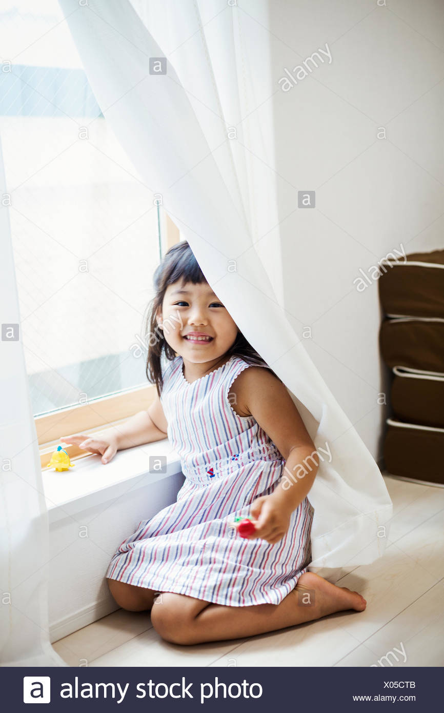 Family home. A girl playing by a window, hiding behind the net curtain. - Stock Image