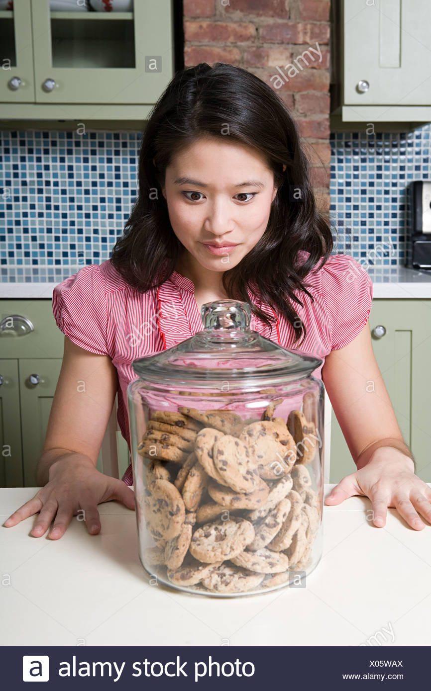 Young woman with cookie jar - Stock Image