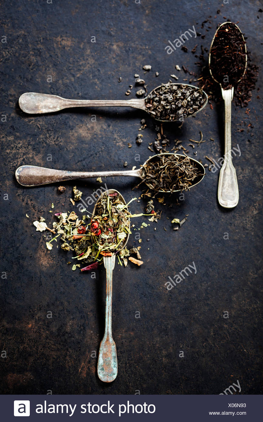 Tea composition with Different kind of tea and old spoons on dark background - Stock Image