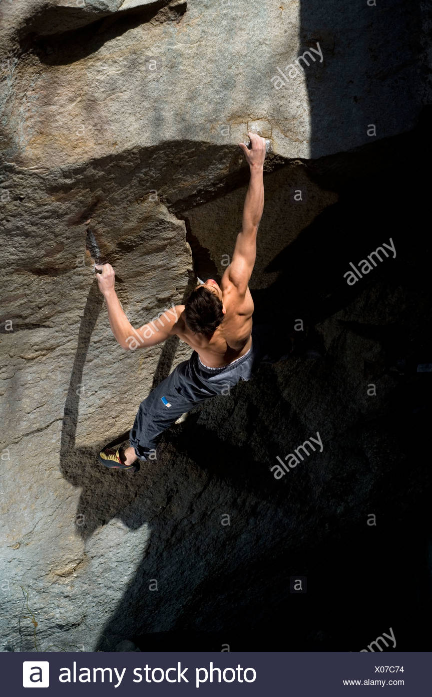A young man climbs a difficult boulder problem during a climbing competition in Tennessee. (artificial lighting) - Stock Image