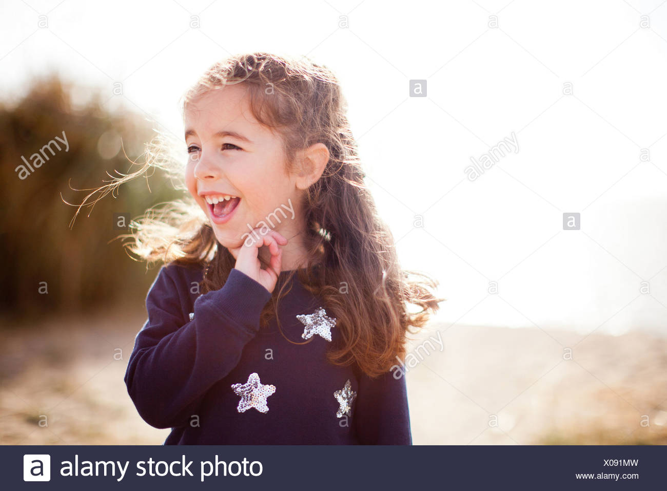 Portrait of girl looking away, laughing - Stock Image