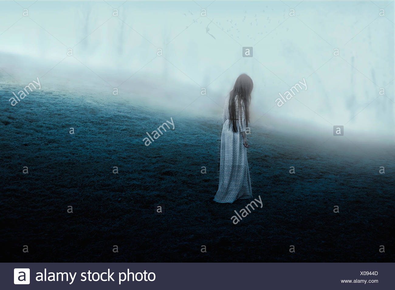 Woman walking on misty hill - Stock Image