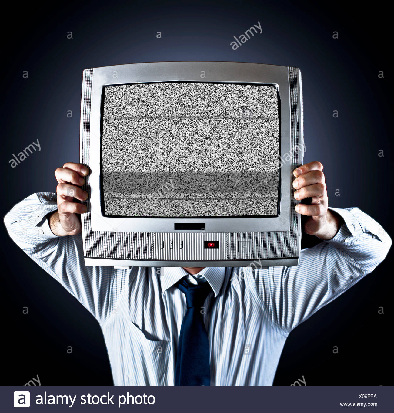 Man holding old fashioned television in front of his face - Stock Image