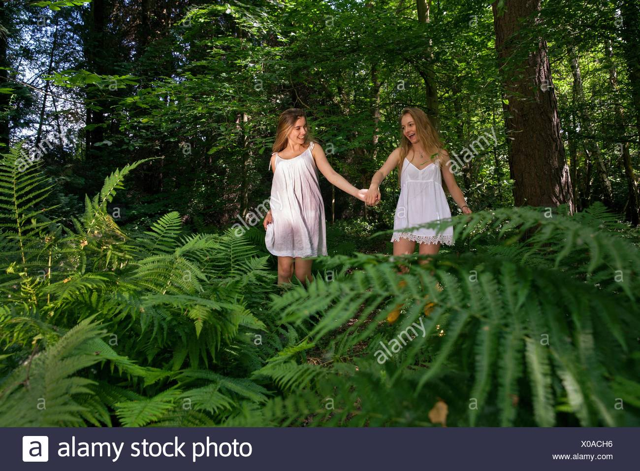 Two teenage girls walking through forest, hand in hand - Stock Image