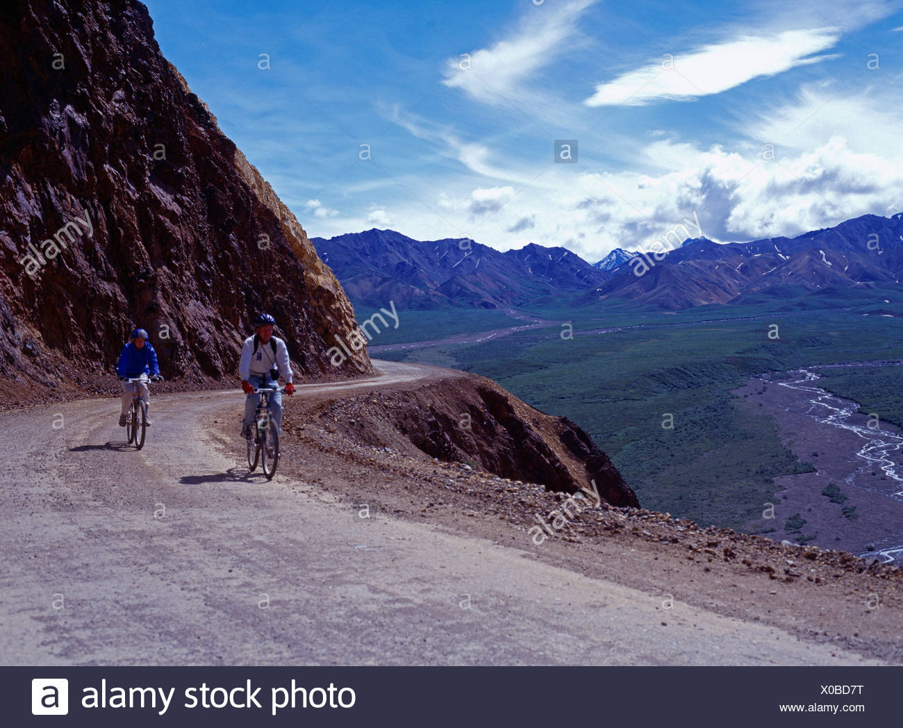 Couple mountain biking park road over Polychrome Pass Denali National Park Alaska. - Stock Image