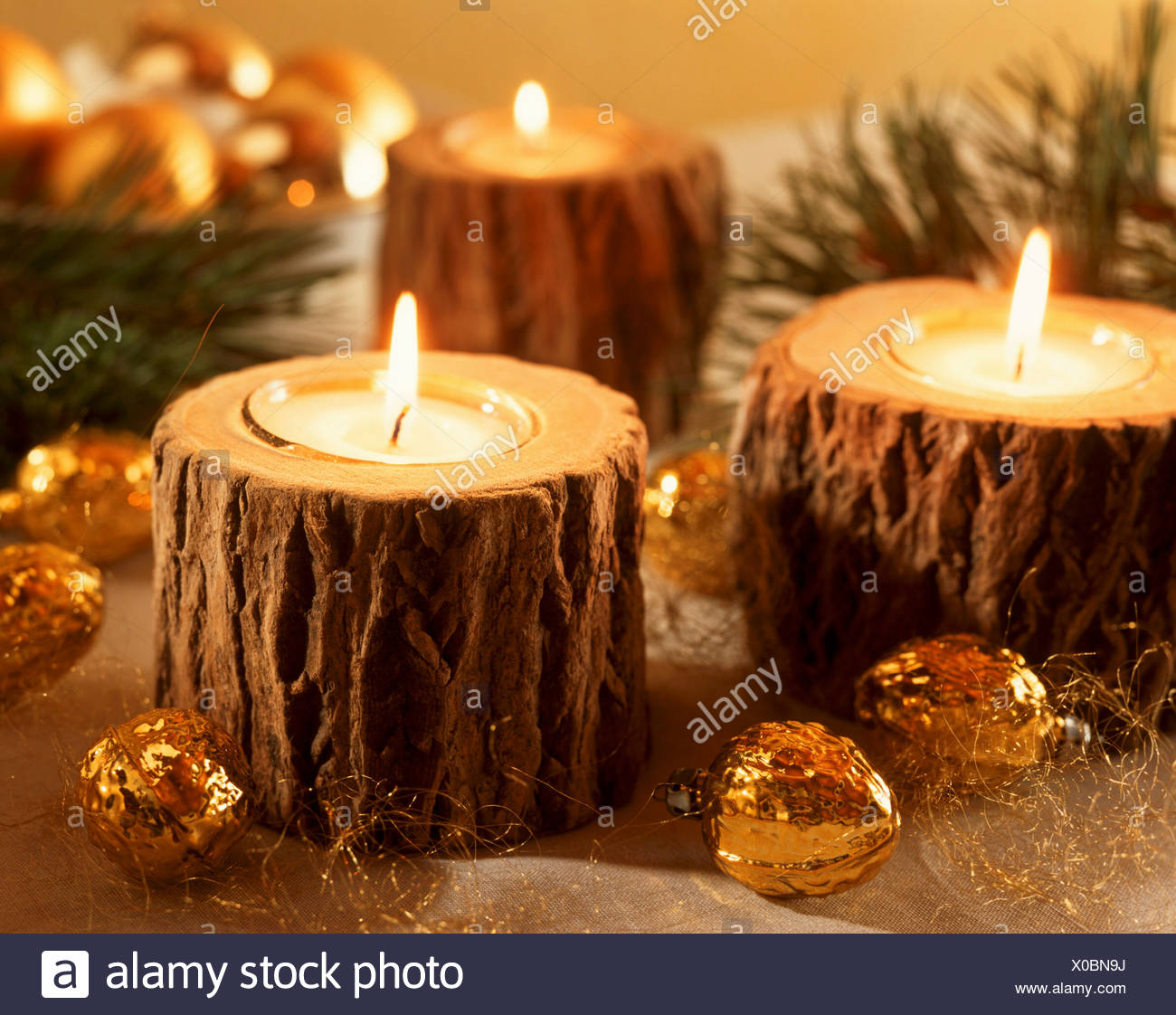 burning tea lights in tree stumps as christmas decorations
