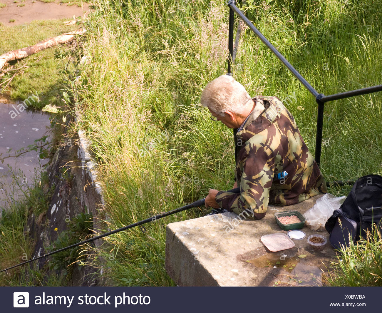 fisherman angling on Lancaster canal - Stock Image