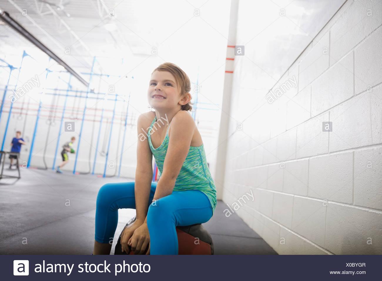 Girl sitting on medicine ball - Stock Image