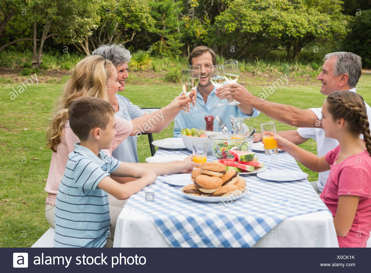 Multi generation family toasting each other at dinner outside - Stock Image