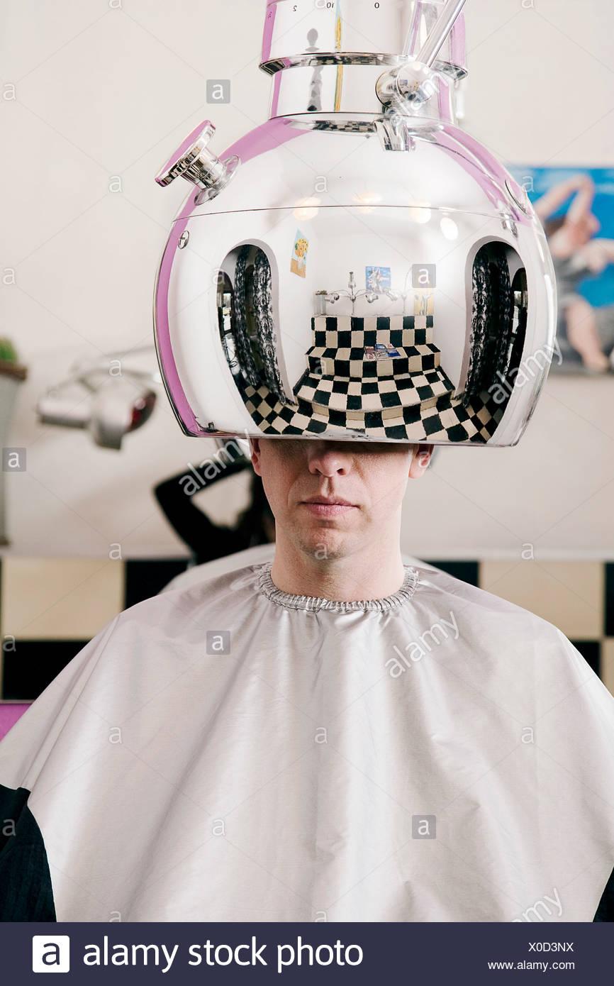portrait of man sitting under hair dryer at hair salon - Stock Image