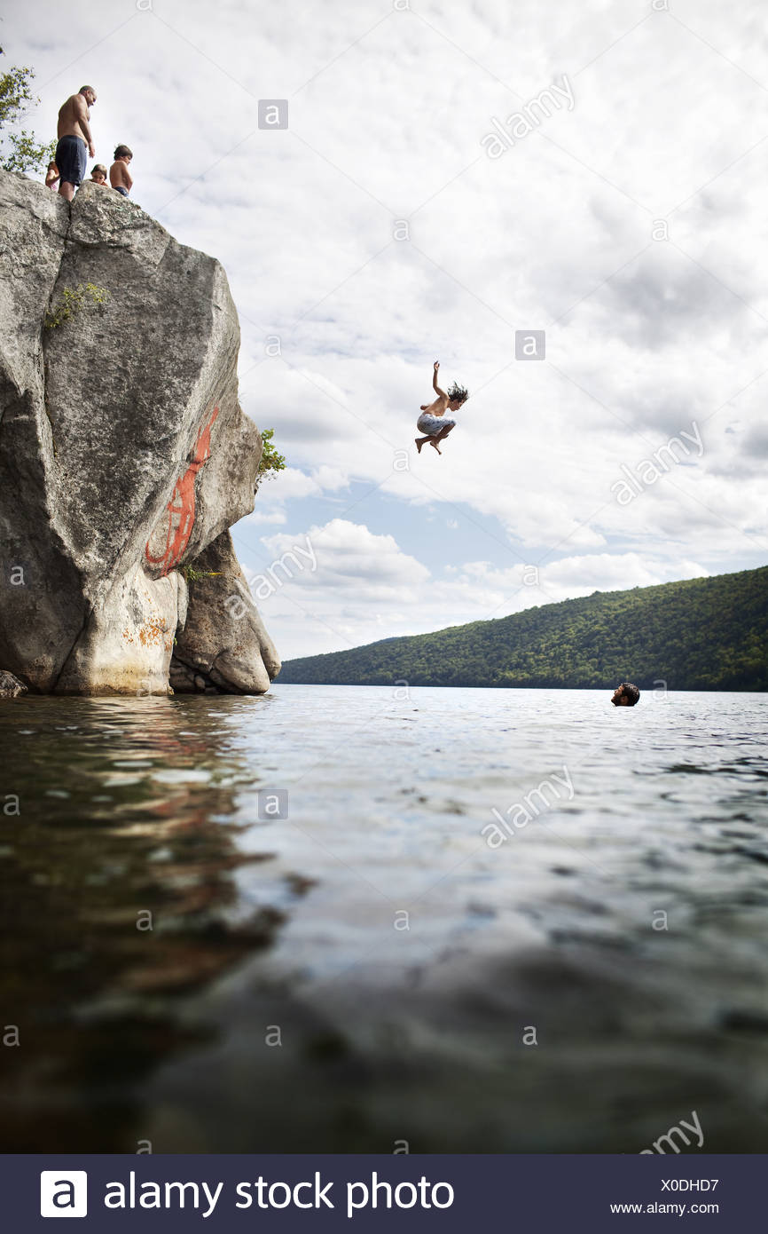 Massachusetts USA group of young people jumping from cliff lake - Stock Image