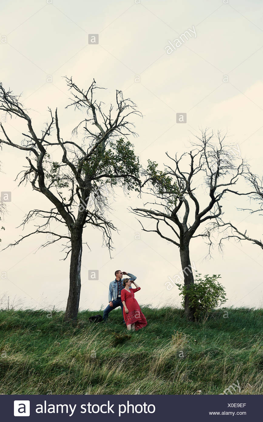 Pregnant couple looking out from hillside - Stock Image