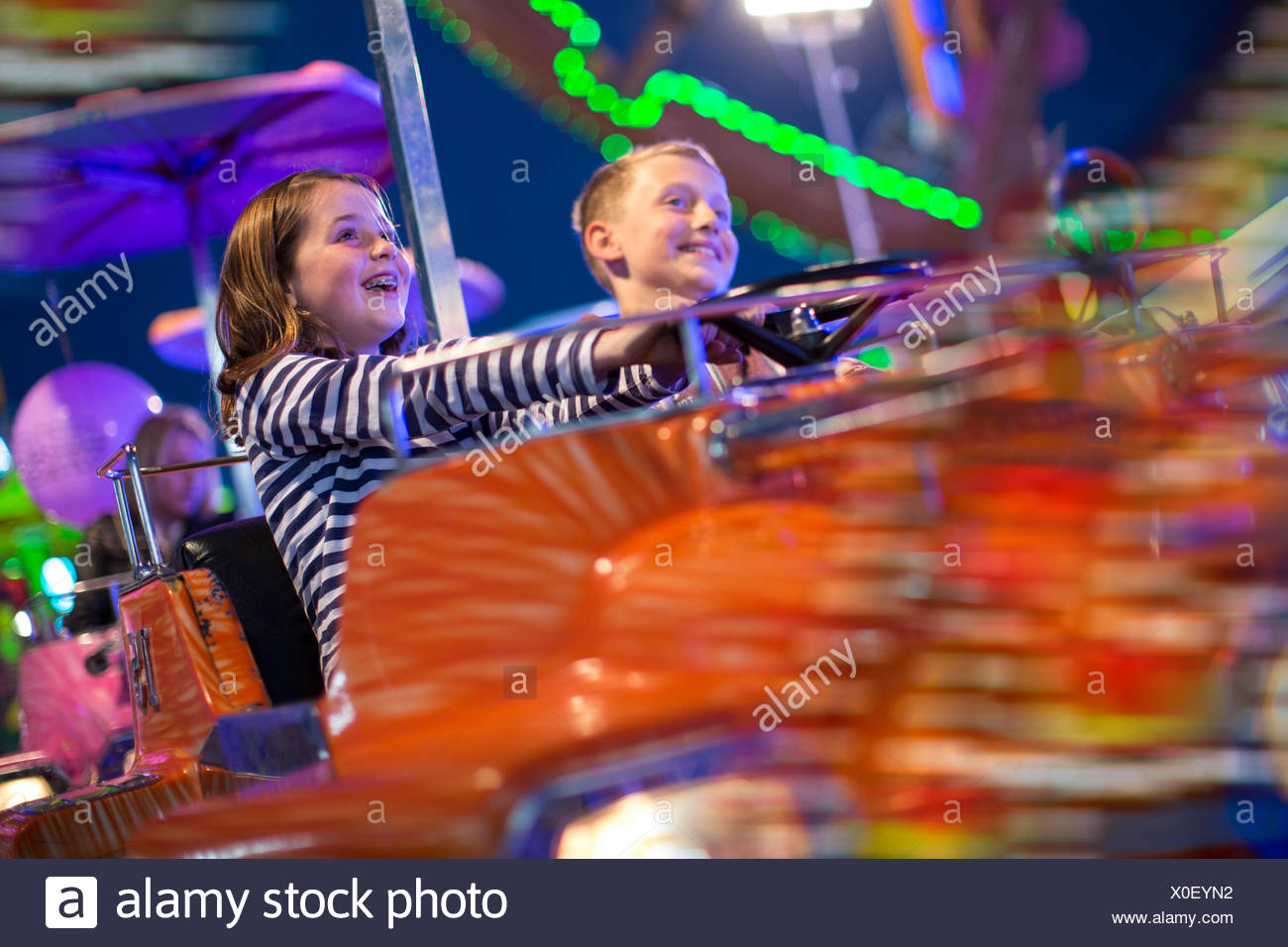 Brother and sister on fairground ride at night - Stock Image