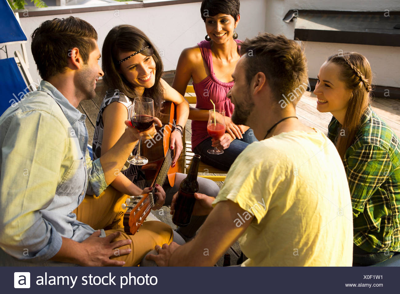 Four friends with drinks, woman playing guitar - Stock Image