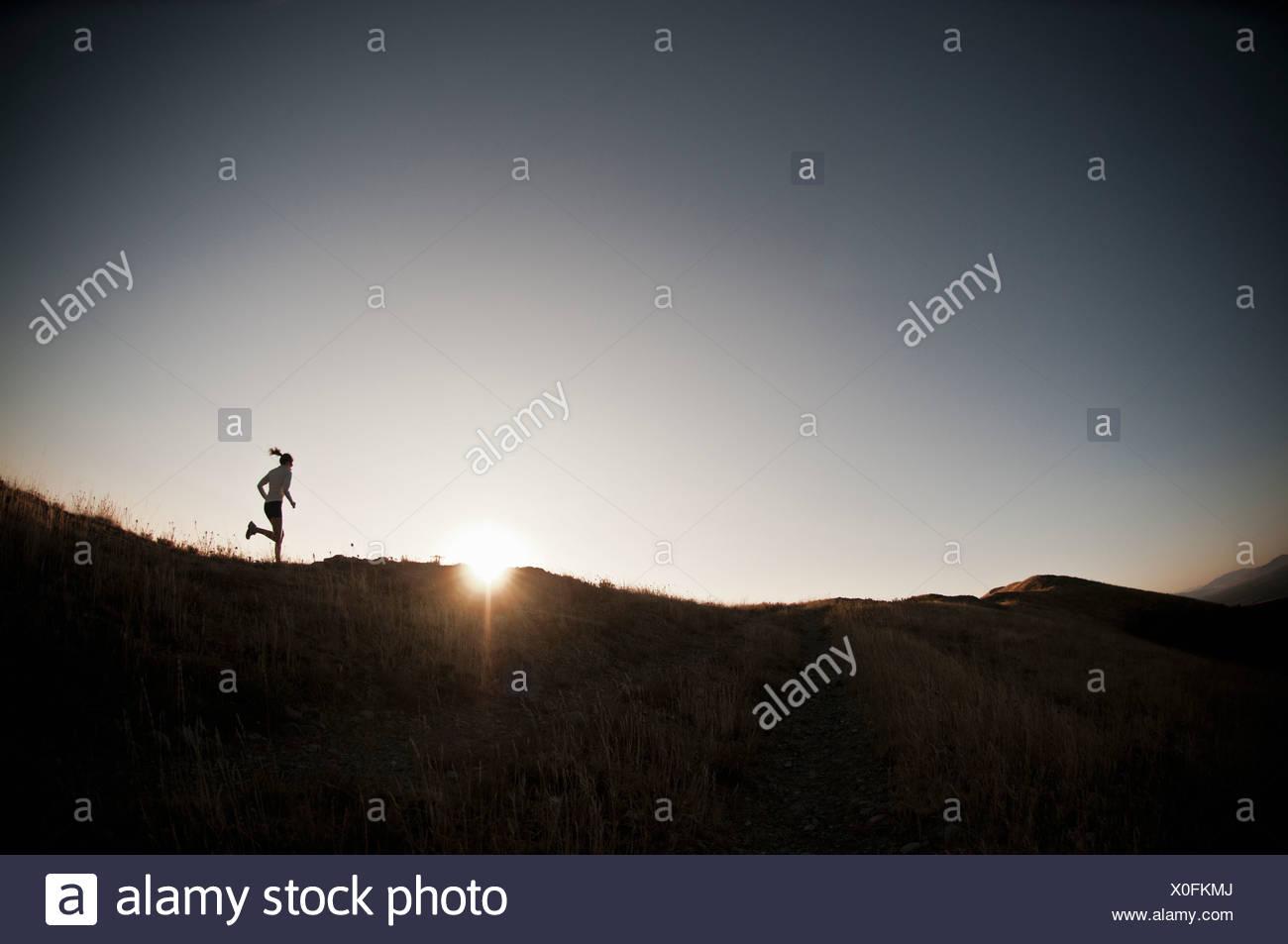 Woman running on dirt path - Stock Image