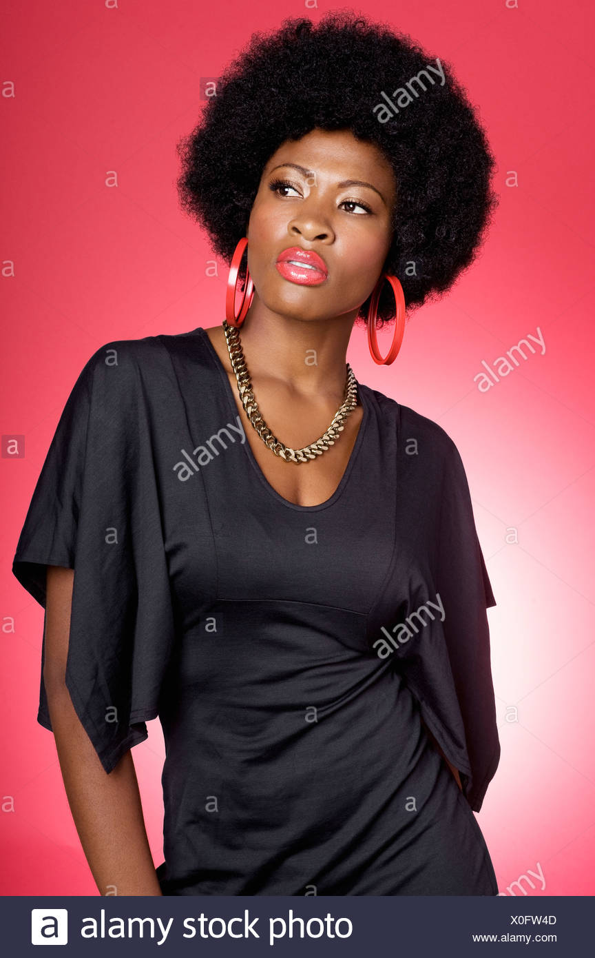 Trendy young African American woman over colored background - Stock Image