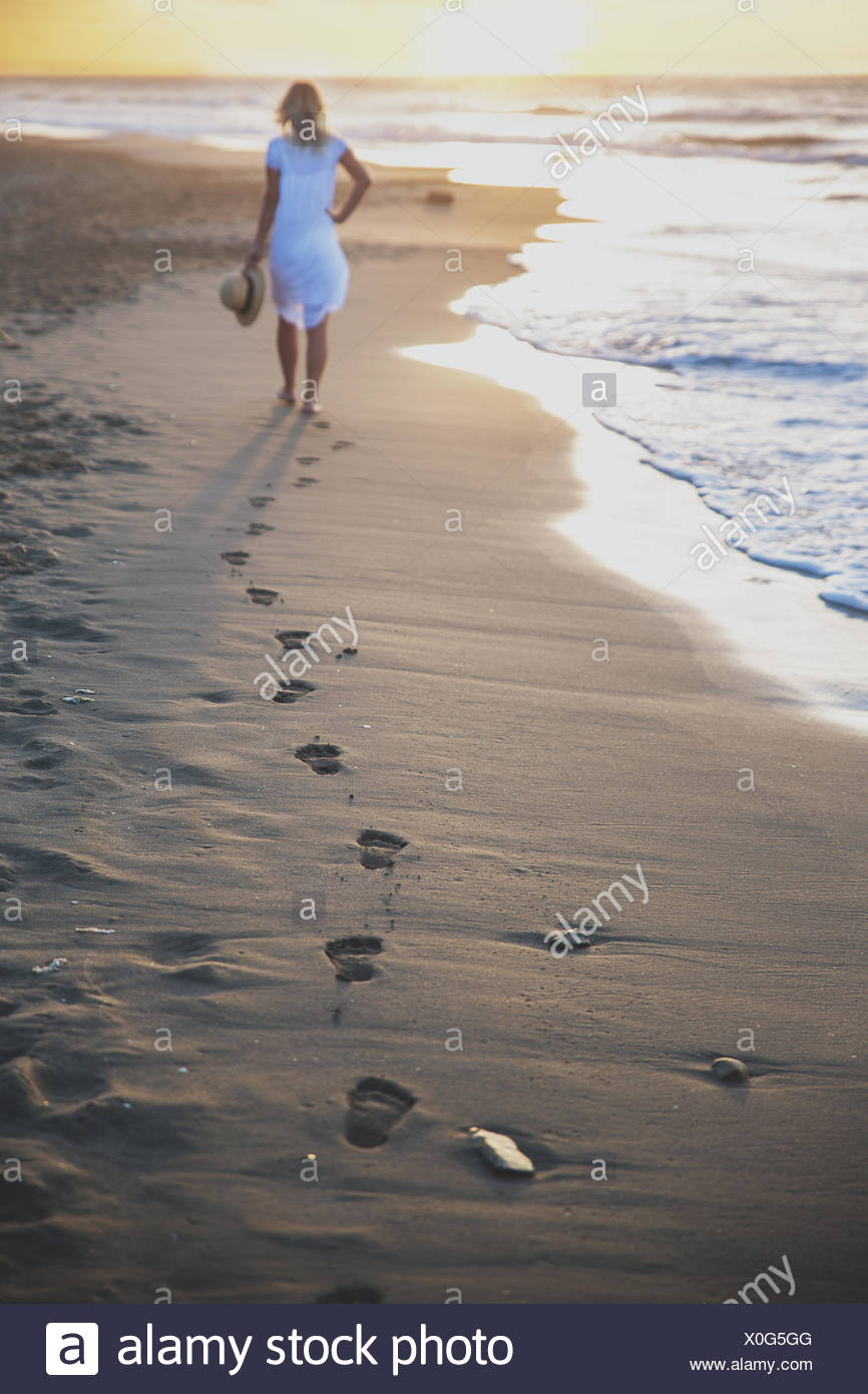 Beautiful woman walking on the beach with her footprints back - Stock Image