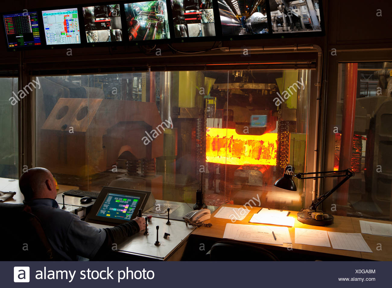 Man working in steelworks control room - Stock Image
