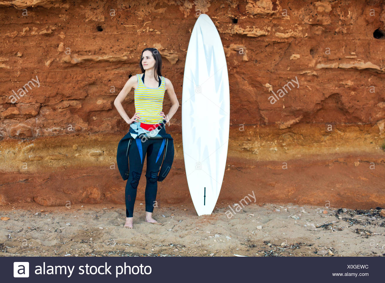 Female Surfer in front of rock - Stock Image