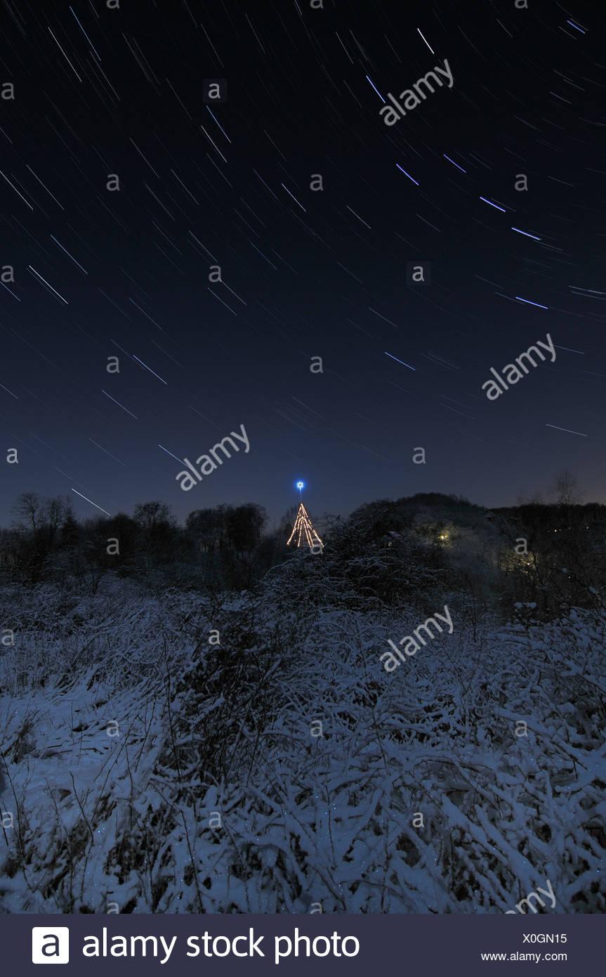 sterrensporen op een heldere winternacht met op de achtergrond een verlichte kerstster startrails on a cold winternight