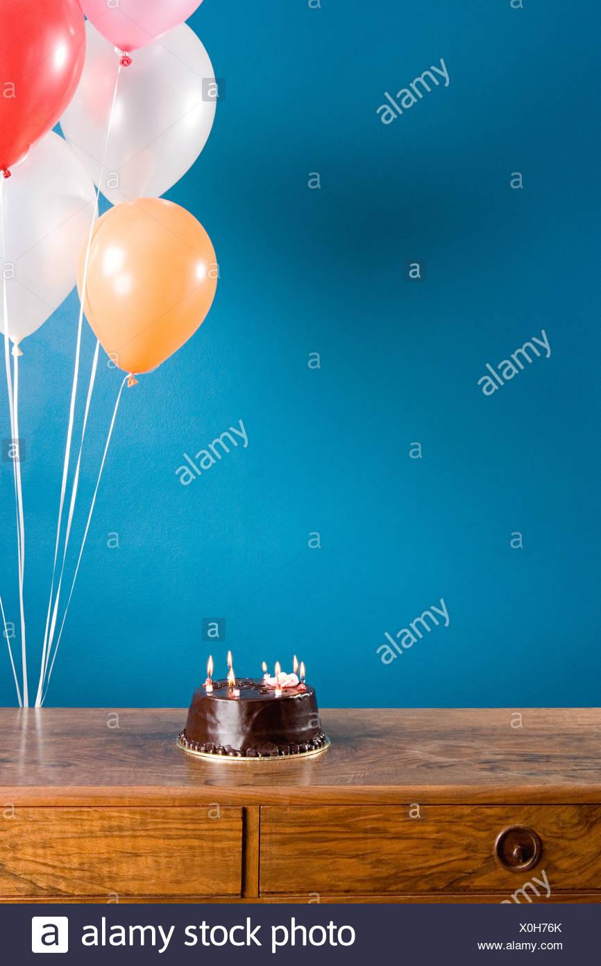 Birthday cake and balloons - Stock Image