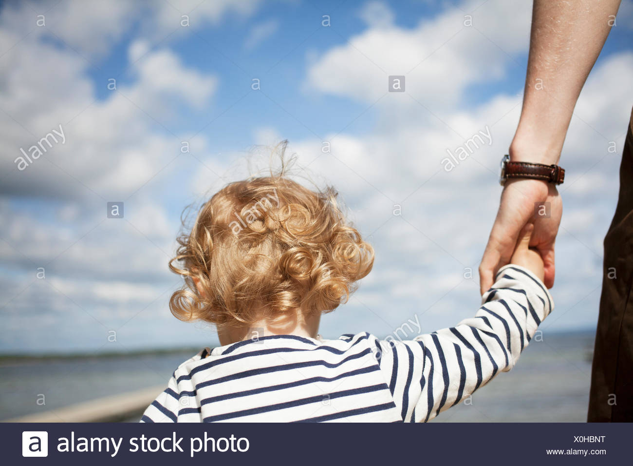 Sweden, Skane, Man holding his daughter´s (2-3) hand - Stock Image