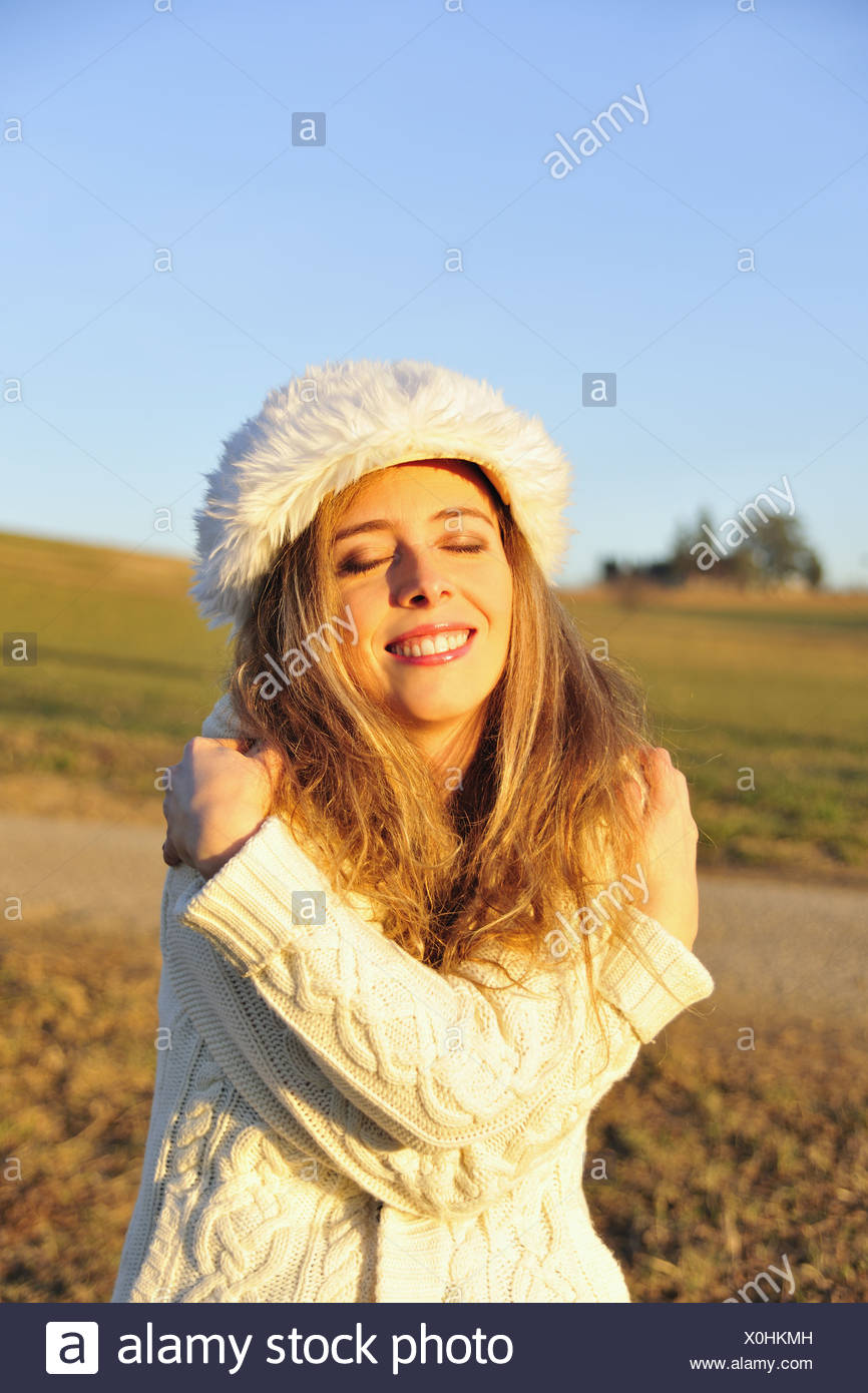 Woman hugging herself outdoors - Stock Image