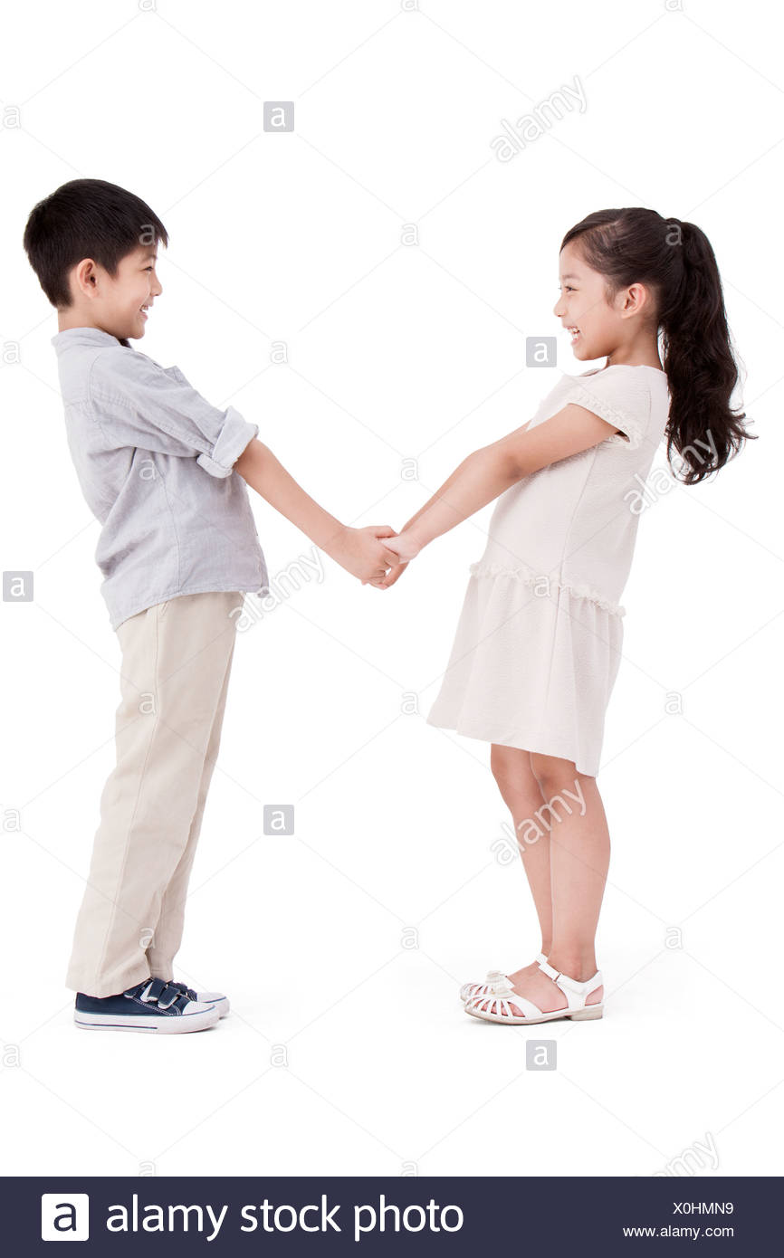 Little Girl And Boy Holding Hands Face To Face Stock Photo