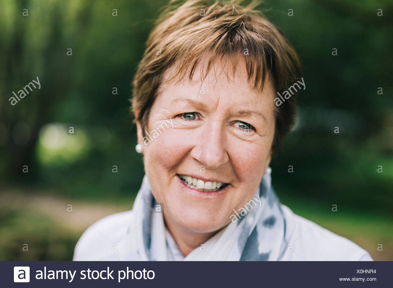 A mature woman with short brown hair smiling. - Stock Image